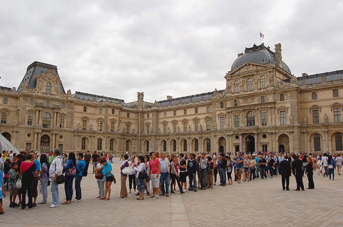 Massen von Touristen stehen vor dem Louvre Schlange