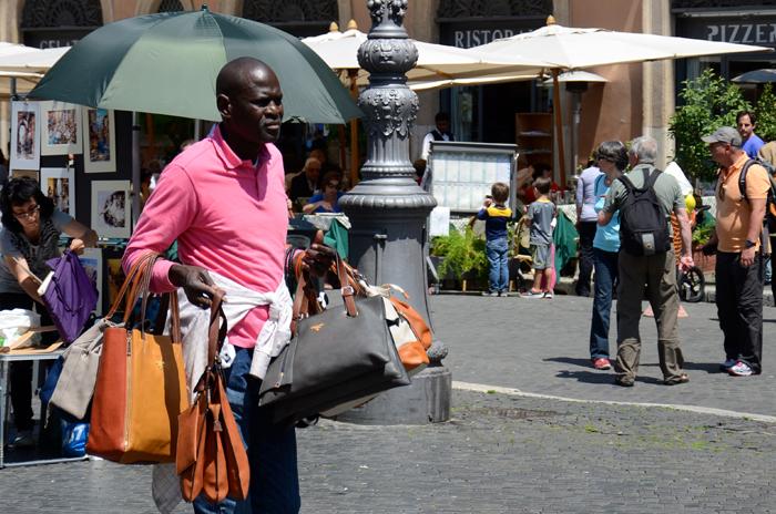 Ein Straßenverkäufer der gefälschte Taschen von großen Marken an Touristen verkauft.