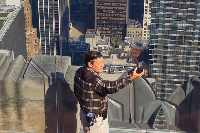 A tourist taking a selfie on top of a skyscraper in New York