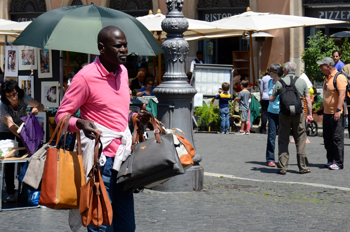 A street vendor selling handbags to a tourist