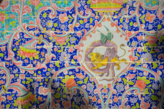 A close shot of tiles showing a dragon and a lion fighting in the Golestan Palace in Tehran
