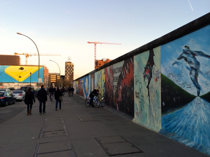 People passing by the East Side Gallery in Berlin